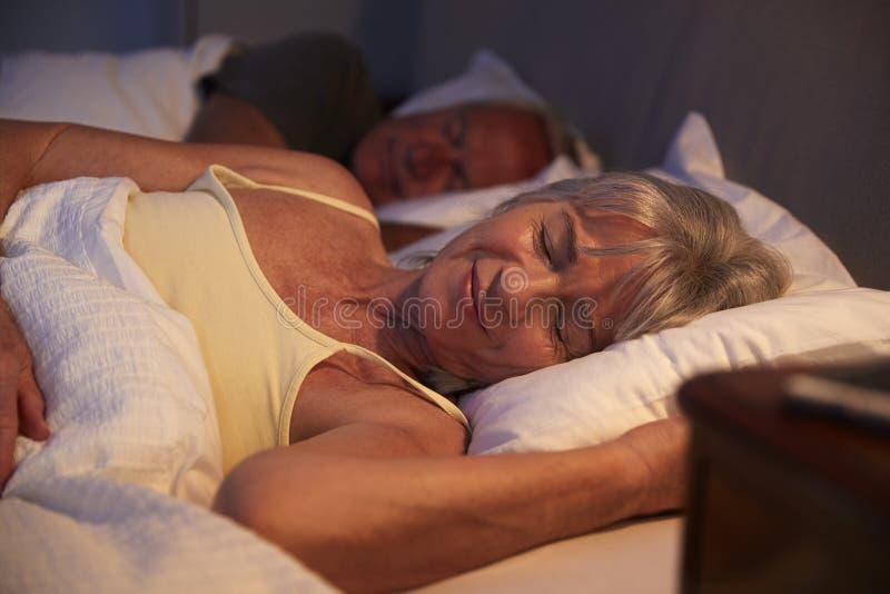 Donna senior pacifica addormentata a letto alla notte fotografia stock libera da diritti