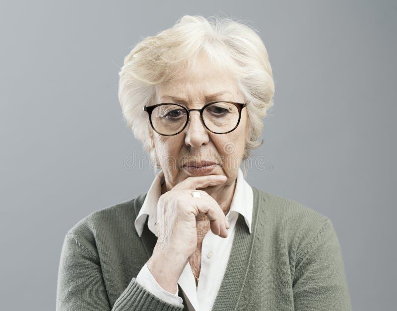 Donna senior pensierosa che pensa con la mano sul mento immagini stock
