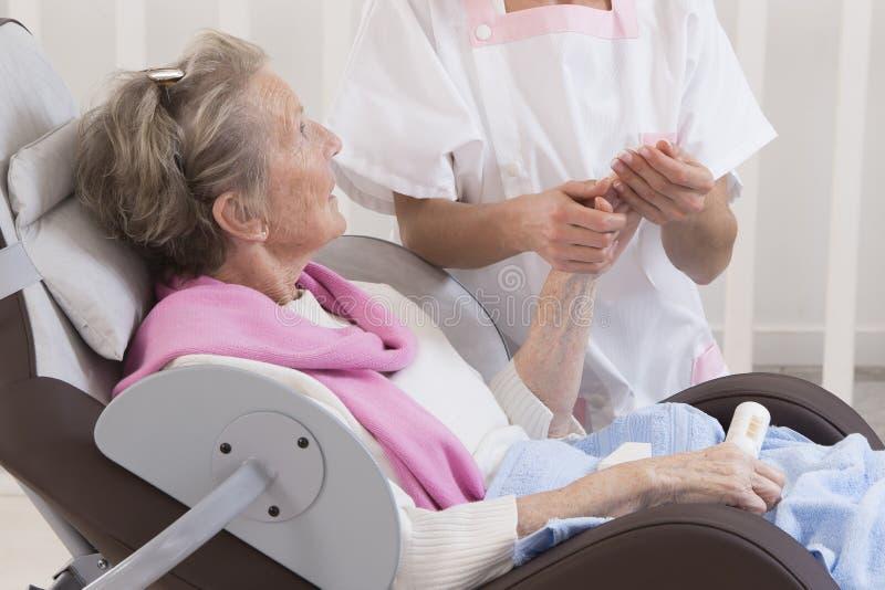 Donna senior più anziana che riceve trattamento domestico di bellezza fotografia stock