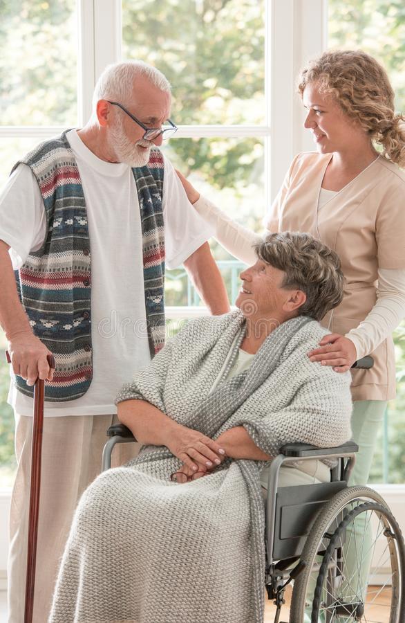 Donna senior positiva sulla sedia a rotelle con l'infermiere preoccupantesi e l'amico anziano con il bastone da passeggio fotografie stock