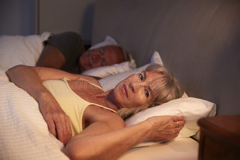 Donna senior preoccupata a letto alla notte che soffre con l'insonnia immagini stock libere da diritti