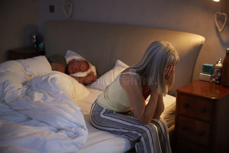 Donna senior preoccupata a letto alla notte che soffre con l'insonnia fotografie stock libere da diritti