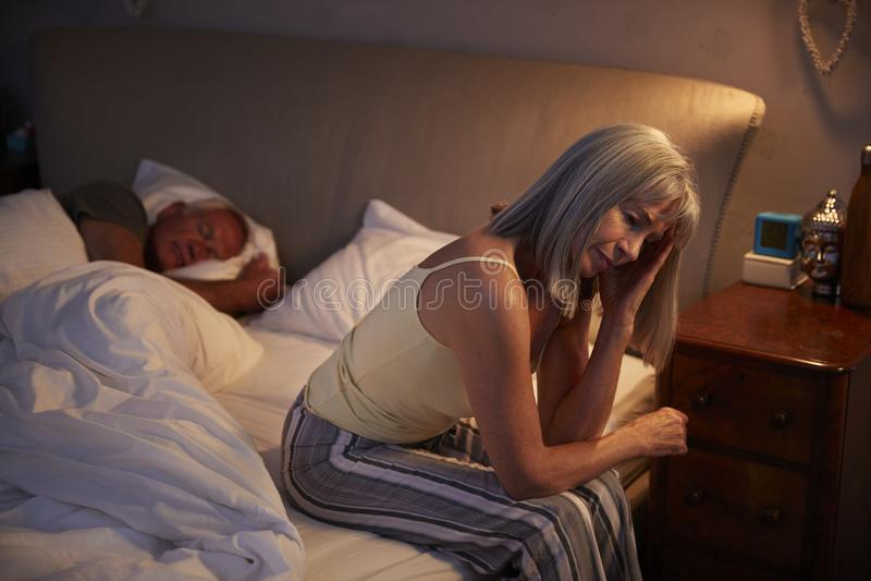 Donna senior preoccupata a letto alla notte che soffre con l'insonnia immagine stock