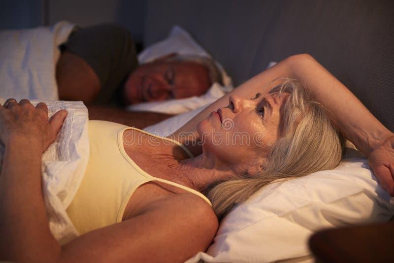 Donna senior preoccupata a letto alla notte che soffre con l'insonnia fotografia stock libera da diritti