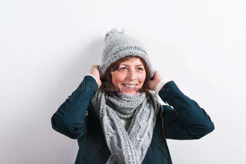 Donna senior in sciarpa e cappello di lana, colpo dello studio immagine stock