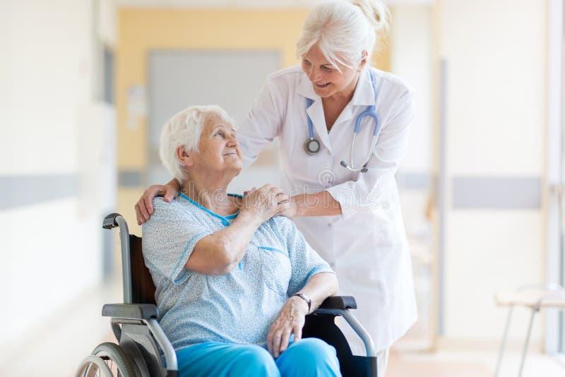 Donna senior in sedia a rotelle con medico femminile in ospedale fotografie stock libere da diritti