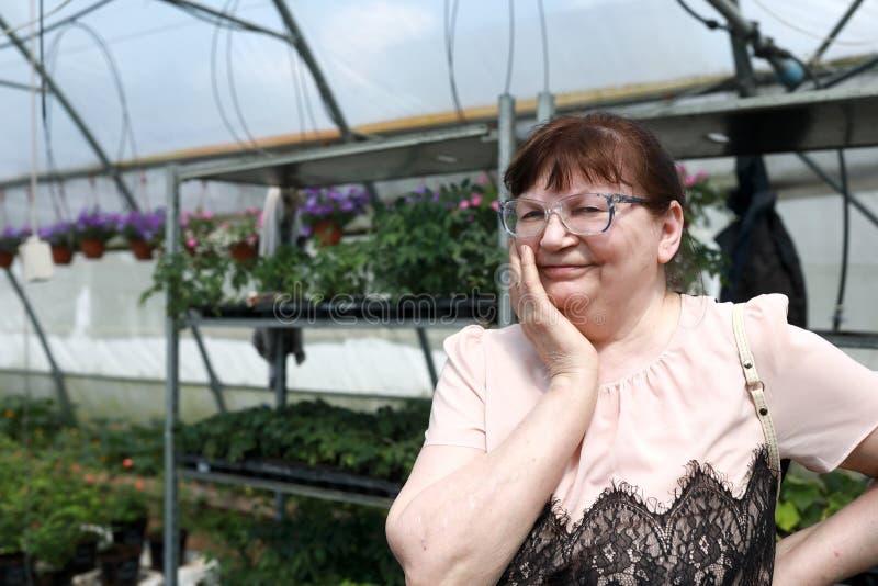 Donna senior in serra dei fiori immagine stock libera da diritti
