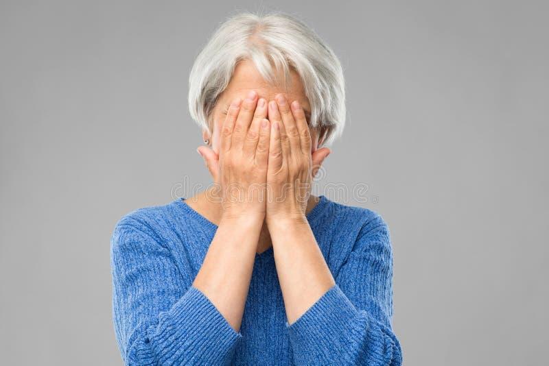 Donna senior sollecitata che tiene alla sua testa immagini stock