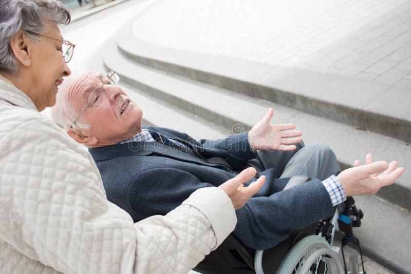 Donna senior sorridente che parla con marito in sedia a rotelle fotografie stock