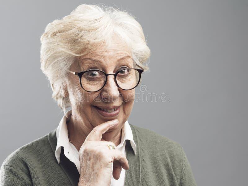 Donna senior sorridente che pensa con la mano sul mento immagine stock
