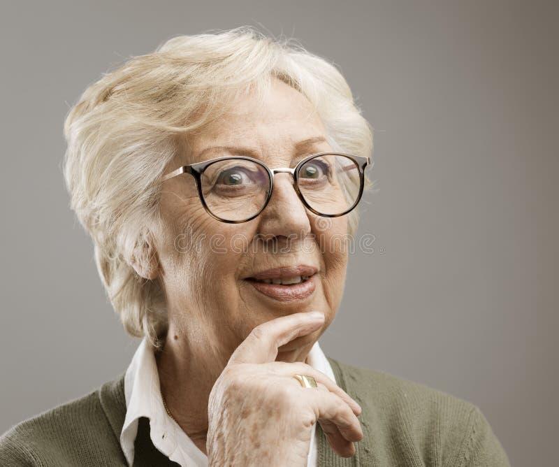 Donna senior sorridente che pensa con la mano sul mento fotografia stock libera da diritti