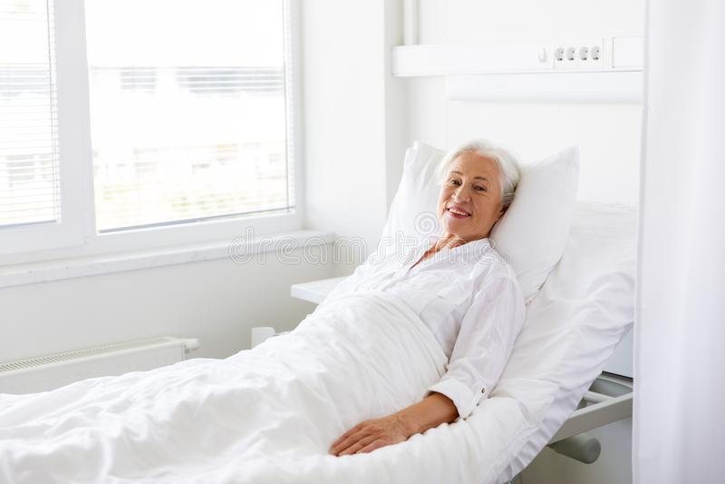 Donna senior sorridente che si trova sul letto al reparto di ospedale fotografie stock