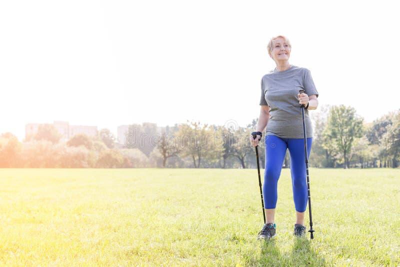 Donna senior sorridente che utilizza i pali di trekking mentre camminando nel parco immagine stock
