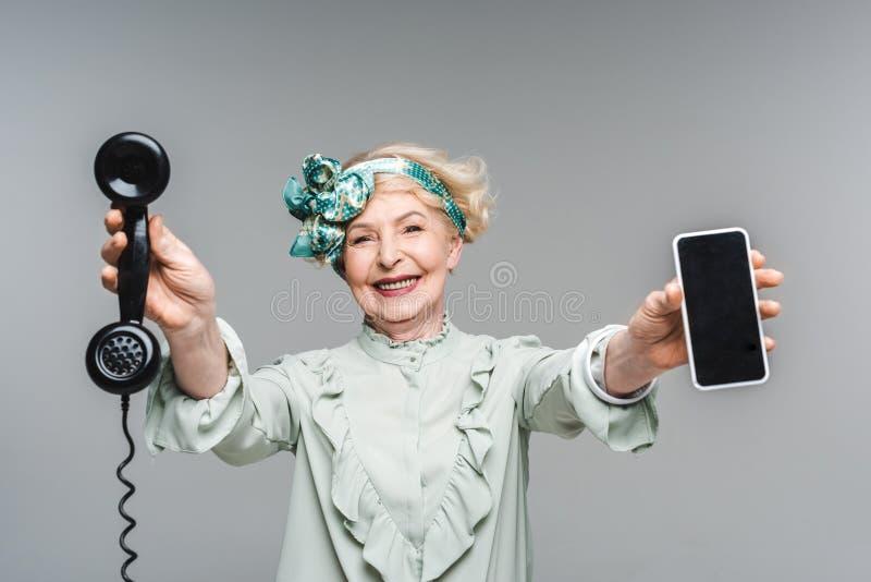 donna senior sorridente con il telefono d'annata e lo smartphone in mani immagine stock libera da diritti