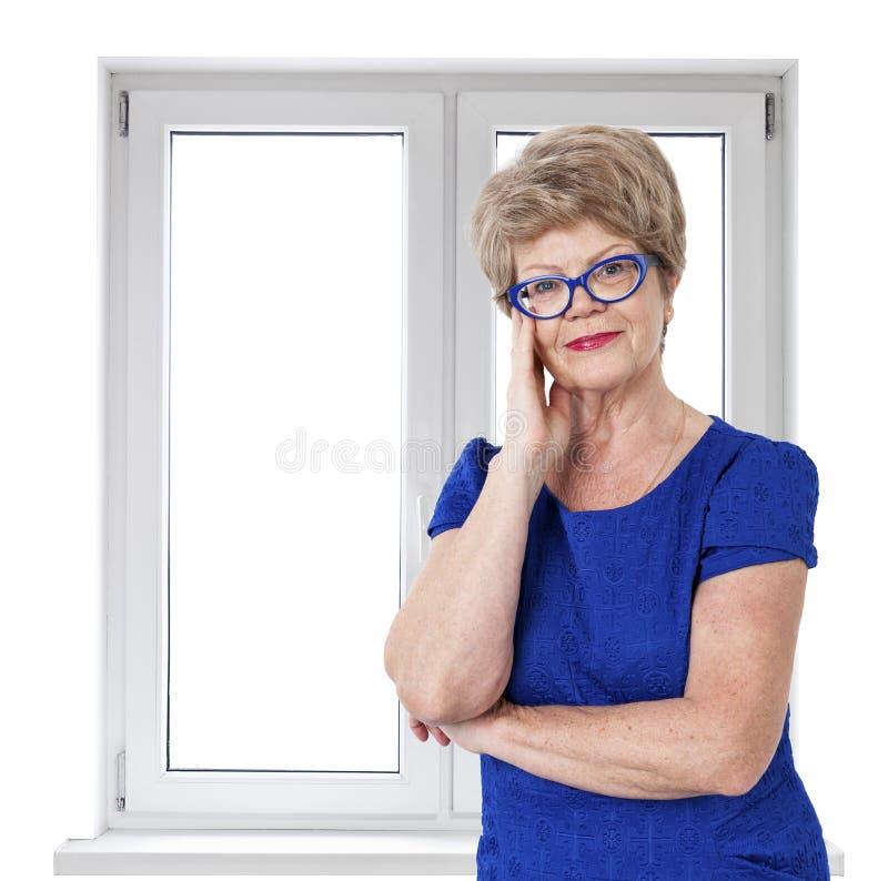 Donna senior sorridente felice che sta il vetro vicino interno del PVC della doppia porta con fondo isolato immagine stock libera da diritti