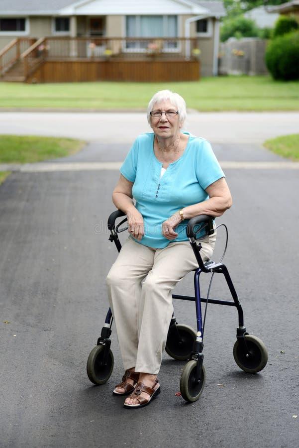 Donna senior stanca che si siede sul camminatore fotografia stock
