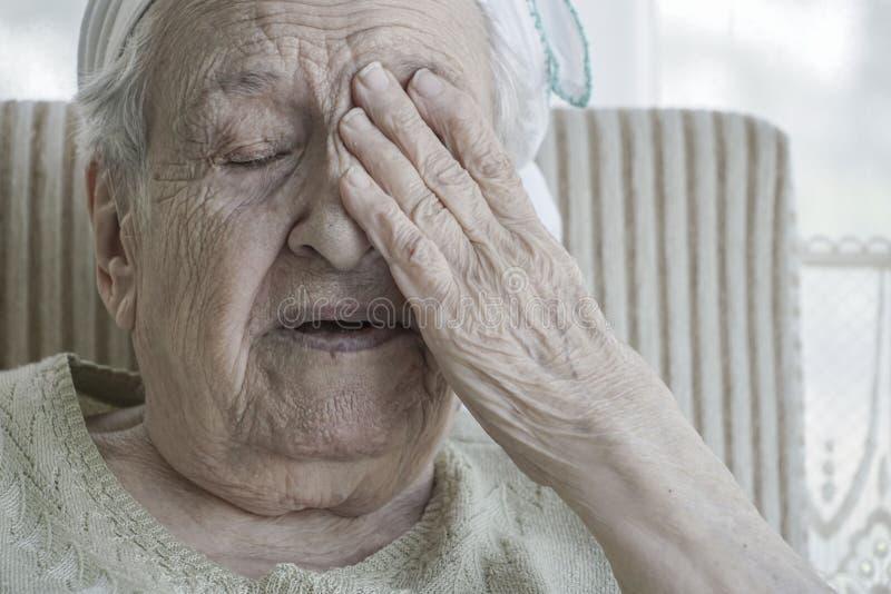 Donna senior stanca chiusa il suo fronte con la sua mano corrugata fotografia stock