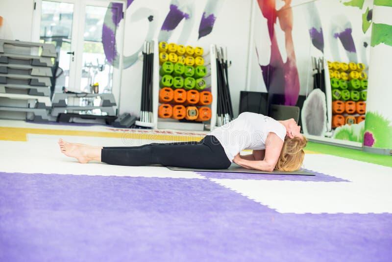 Donna senior su una classe di yoga fotografia stock libera da diritti