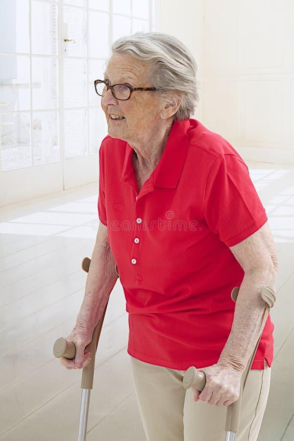 Donna senior sulle grucce fotografie stock libere da diritti