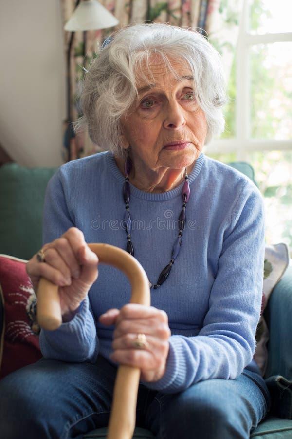 Donna senior triste che si siede in canna di camminata della tenuta della sedia fotografie stock