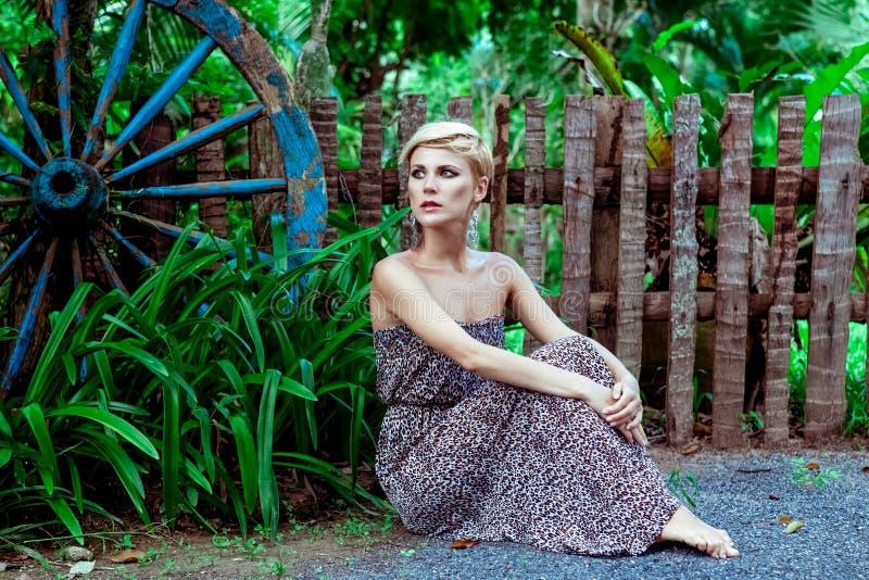 Donna sensuale che si siede nella foresta fotografia stock