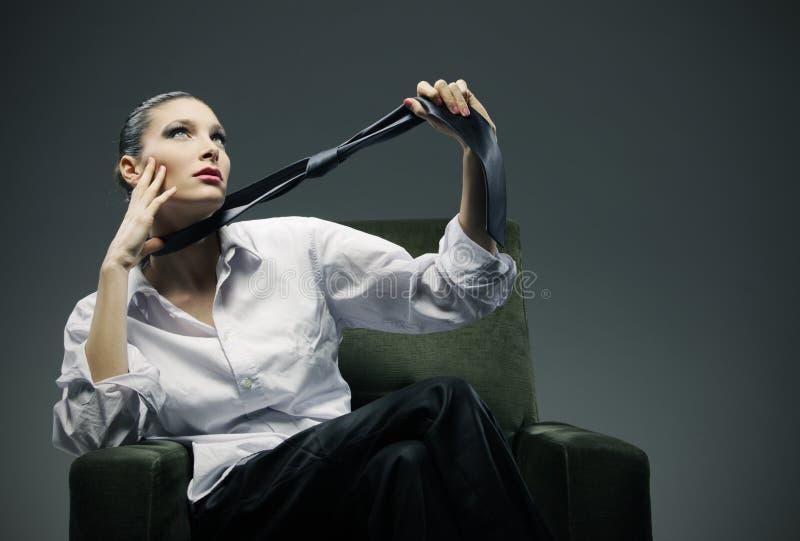 Donna sensuale che si siede in una poltrona fotografie stock libere da diritti