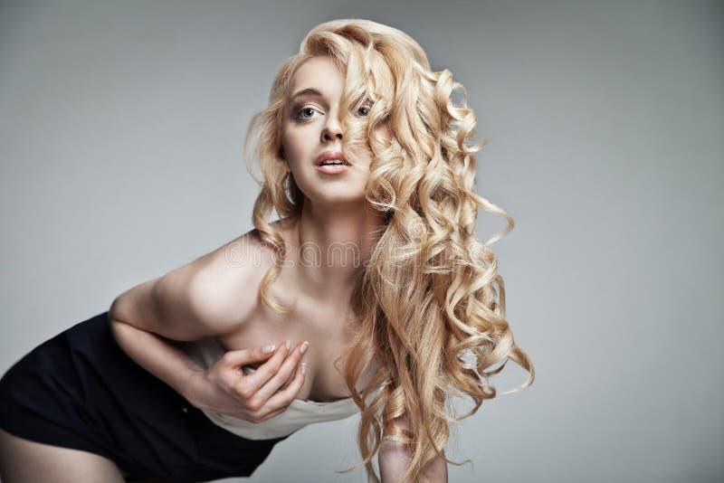 Donna sensuale con capelli biondi lunghi ricci brillanti fotografia stock
