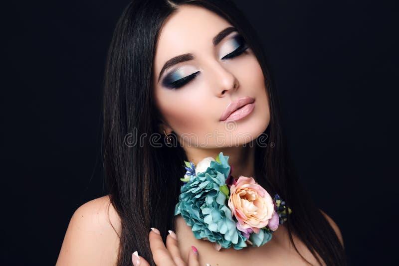 Donna sensuale con capelli neri diritti con la collana luminosa del fiore e di trucco fotografie stock libere da diritti