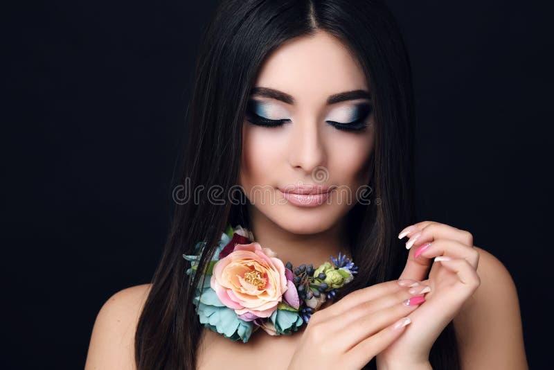Donna sensuale con capelli neri diritti con la collana luminosa del fiore e di trucco immagini stock
