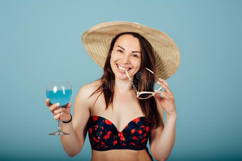 Donna sensuale con gli occhiali da sole che beve un cocktail fotografia stock