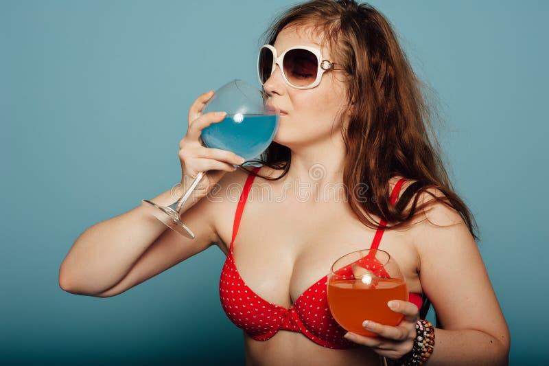 Donna sensuale con gli occhiali da sole che beve un cocktail fotografia stock libera da diritti