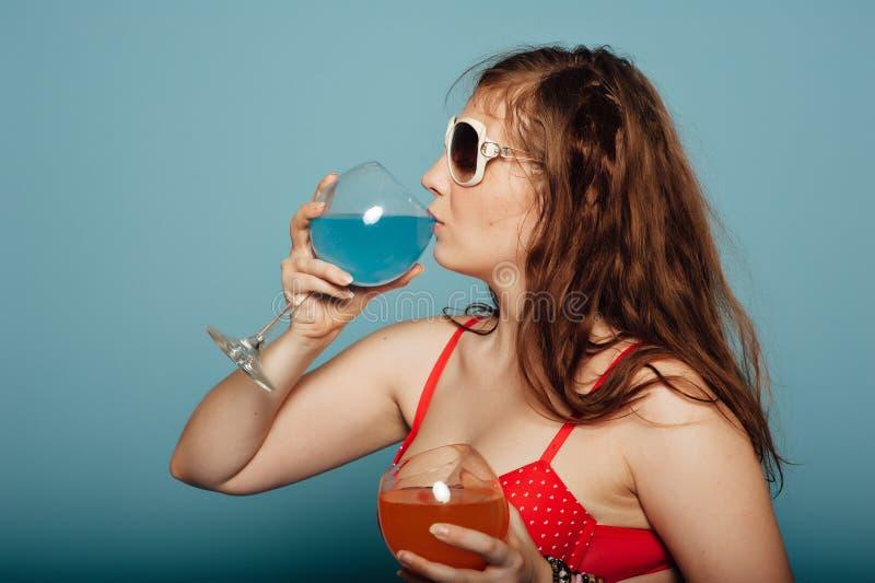 Donna sensuale con gli occhiali da sole che beve un cocktail fotografie stock libere da diritti