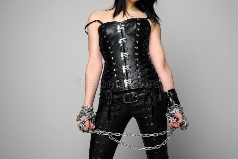 Donna sensuale in corsetto e pantaloni di cuoio neri con la catena a disposizione fotografia stock libera da diritti