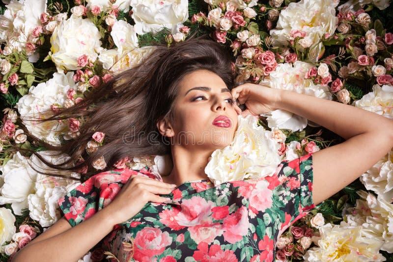 Donna sensuale seducente di Attactive che si trova sui fiori immagini stock libere da diritti