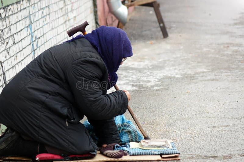 Donna senza tetto triste che si siede sulla gente della via che passa vicino immagine stock libera da diritti