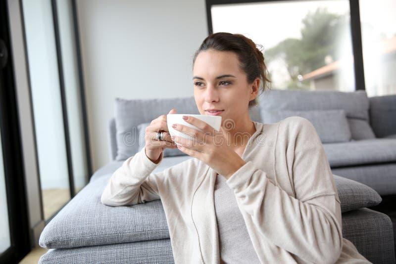 Donna serena che mangia una tazza di tè immagini stock libere da diritti