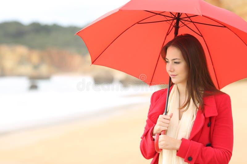 Donna seria che contempla la spiaggia nell'inverno immagini stock libere da diritti