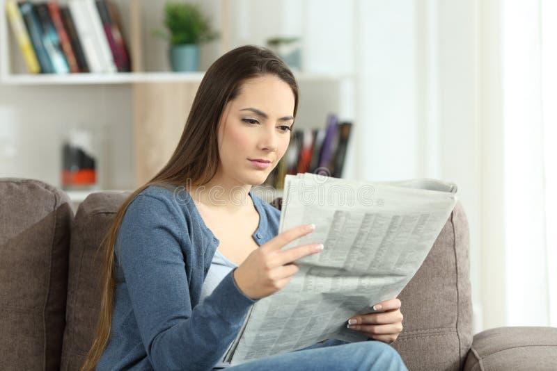 Donna seria che legge un giornale su uno strato fotografia stock libera da diritti