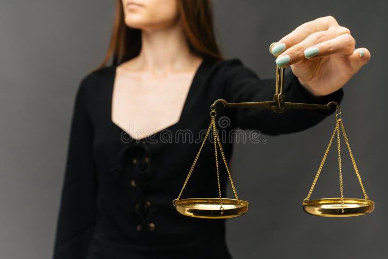 Donna seria che tiene la scala della giustizia su fondo scuro immagine stock libera da diritti