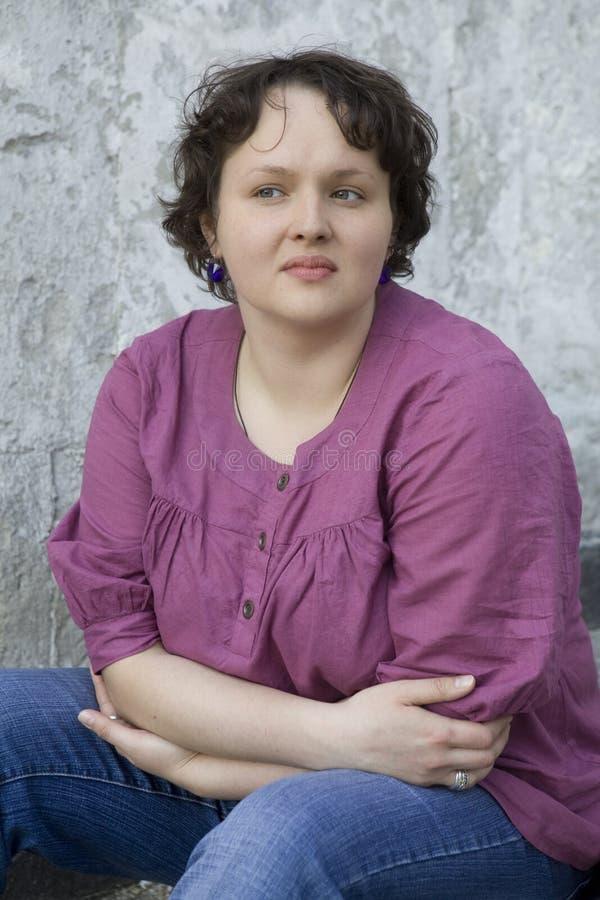 Donna seria dell'arricciatura che si siede sulle scale fotografia stock libera da diritti