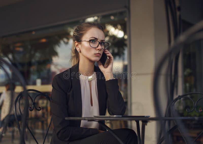 Donna seria di affari in vestito che parla sul cellulare immagini stock