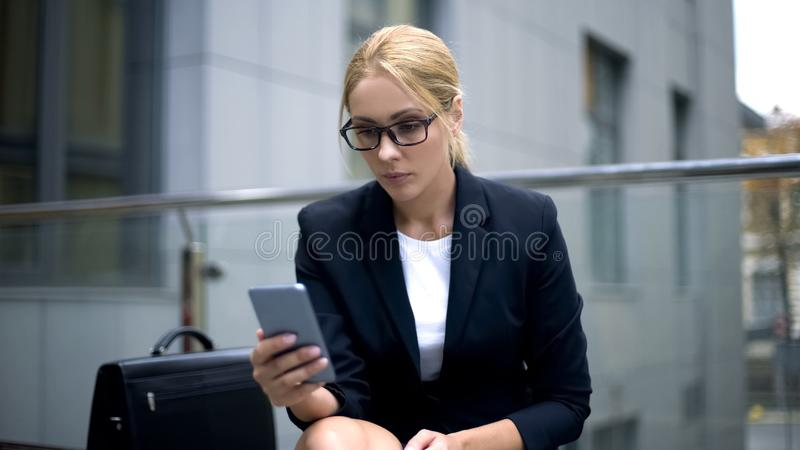 Donna seria in occhiali facendo uso del telefono, problemi di vista a causa di lavoro eccessivo immagini stock libere da diritti