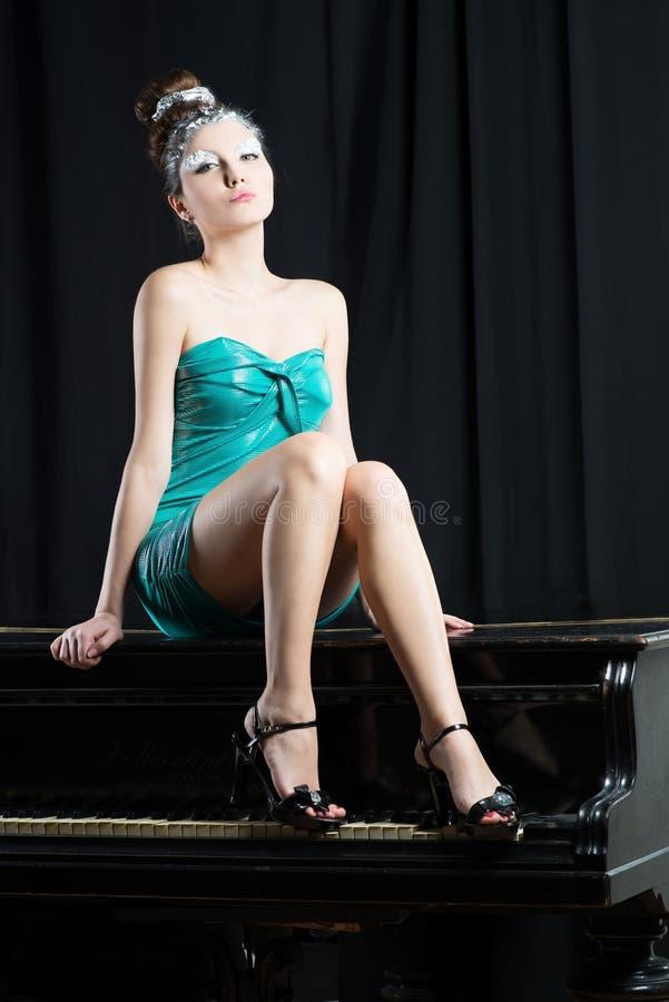 Donna sessuale in breve mini vestito blu che si siede sul piano immagini stock libere da diritti