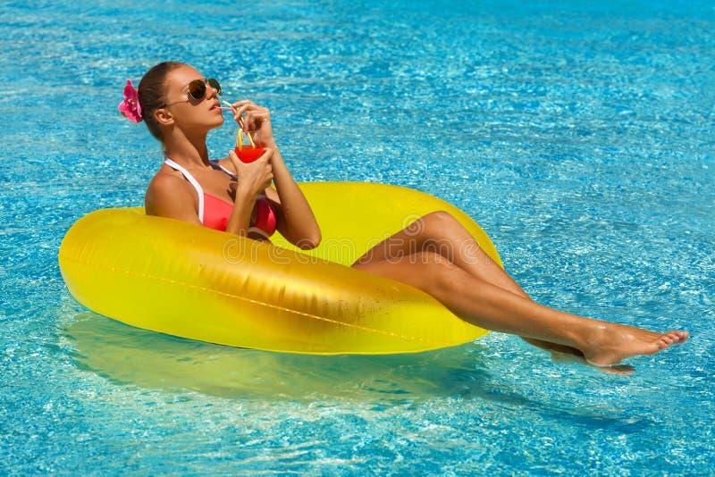 Donna sexy in bikini che gode del sole di estate e che si abbronza durante le feste in stagno con un cocktail fotografia stock