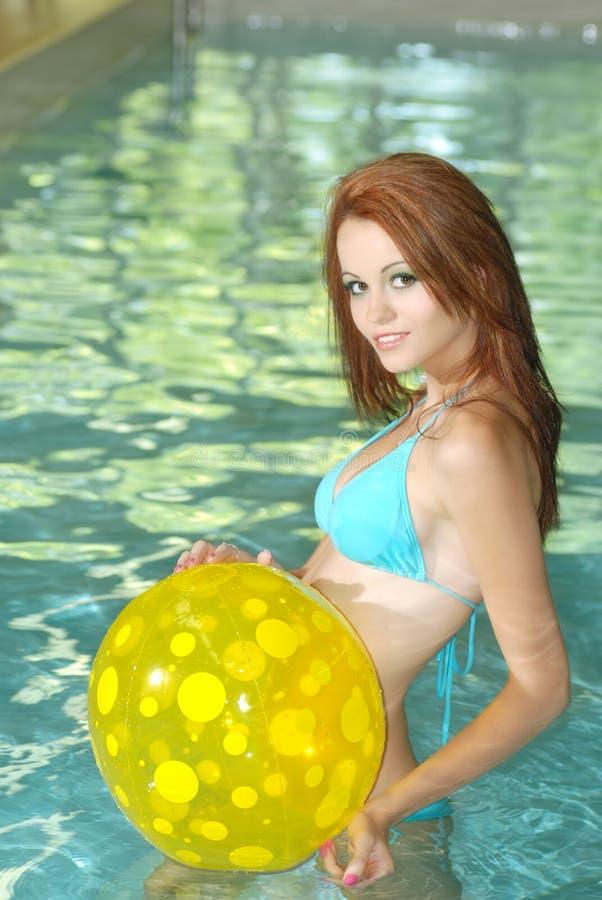 Donna sexy che gioca con la sfera di spiaggia gialla in raggruppamento fotografia stock libera da diritti