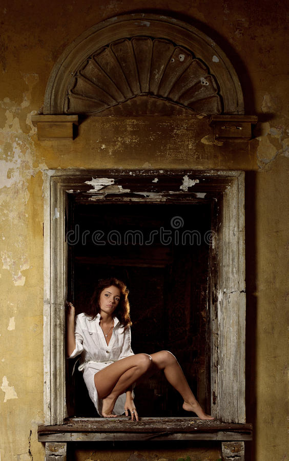 Donna sexy che propone nella finestra fotografia stock