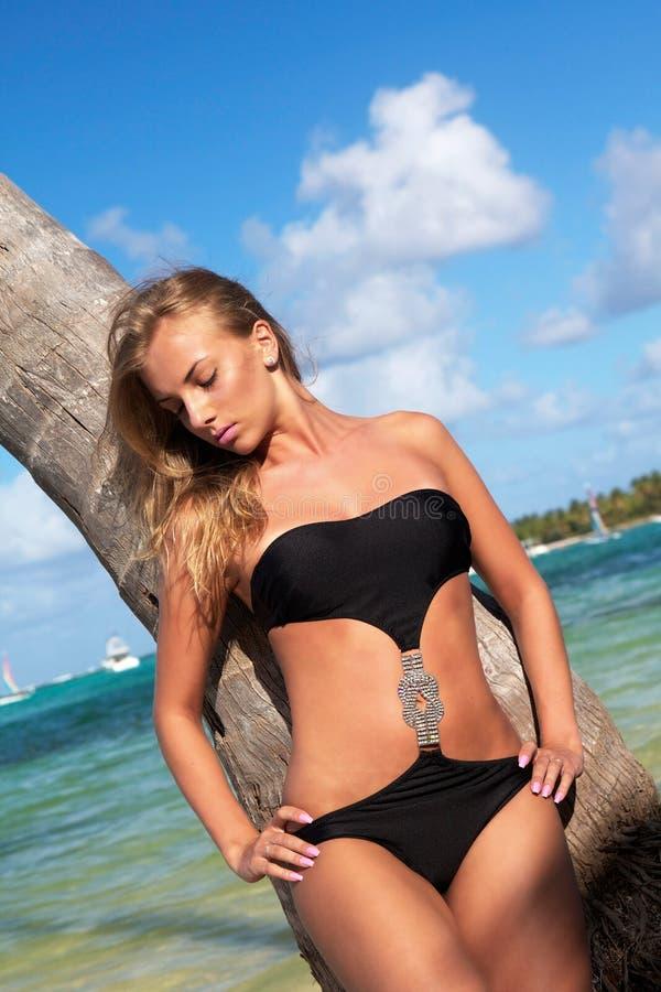 Donna sexy che si distende sulla palma su una spiaggia caraibica immagini stock libere da diritti