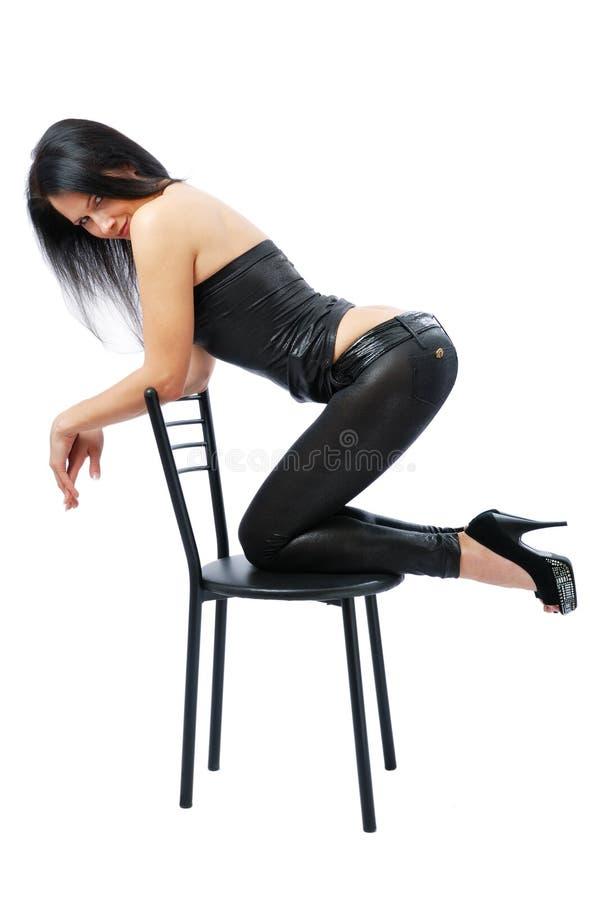 Donna sexy che si inginocchia sulla presidenza fotografie stock libere da diritti
