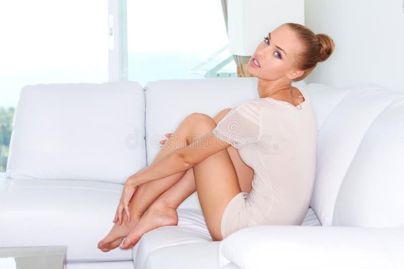 Donna sexy che si siede su un sofà bianco immagine stock