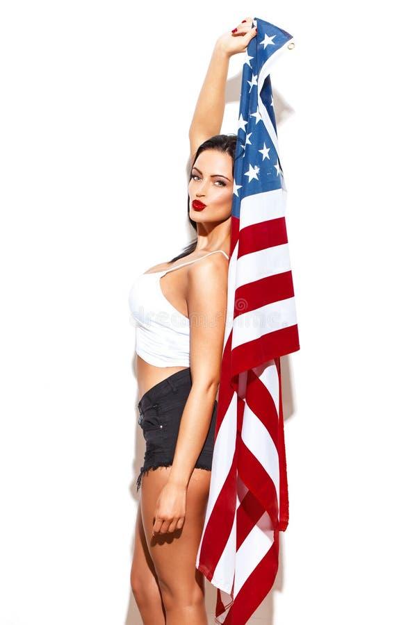 Donna sexy che tiene la bandiera di U.S.A. alla parete bianca immagine stock